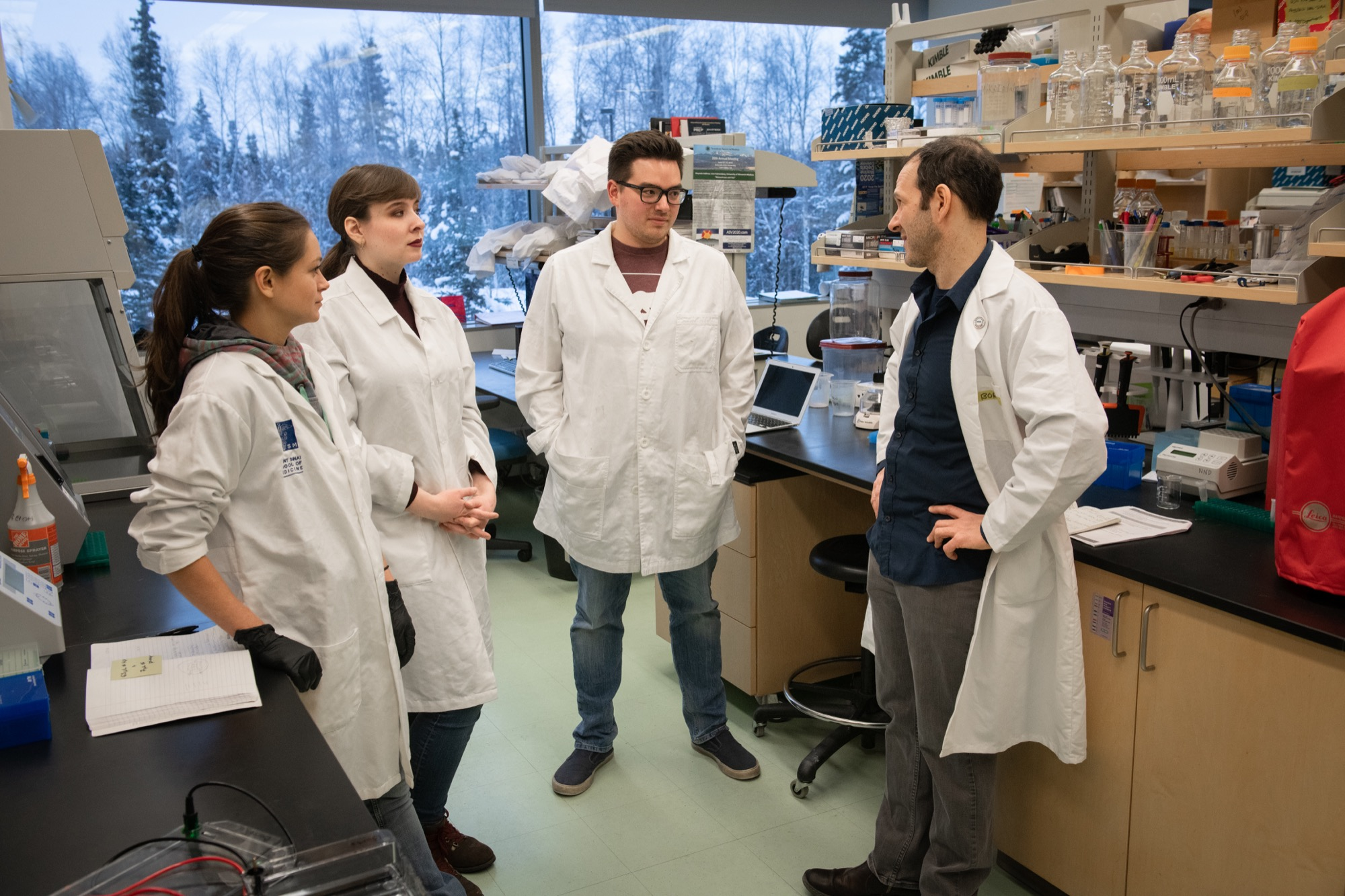 Four researchers discussing coronavirus