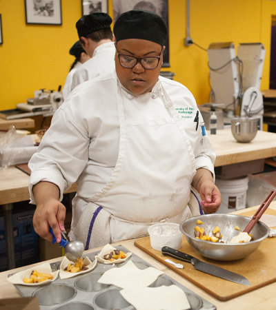 Joycelyn Weaver works on her dessert during the mystery ingredient final at UAA