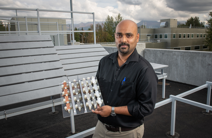 Assistant professor of mechanical engineering Raghu Srinivasan holds a sample of alloy metals to be tested on an adjustable atmospheric corrosion test rack atop UAA's Engineering and Computation Building's parking garage. The rack, which holds material samples at various angles for testing corrosion in cold climates, was designed and built by students led by Srinivasan and received a 2019 Materials Performance Corrosion Innovation of the Year Award. (Photo by James Evans / University of Alaska Anchorage)