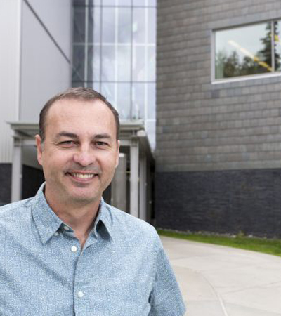 Geology professor Dr. Simon Kattenhorn poses for a picture outside the ConocoPhillips Integrated Science Building on UAA's campus.
