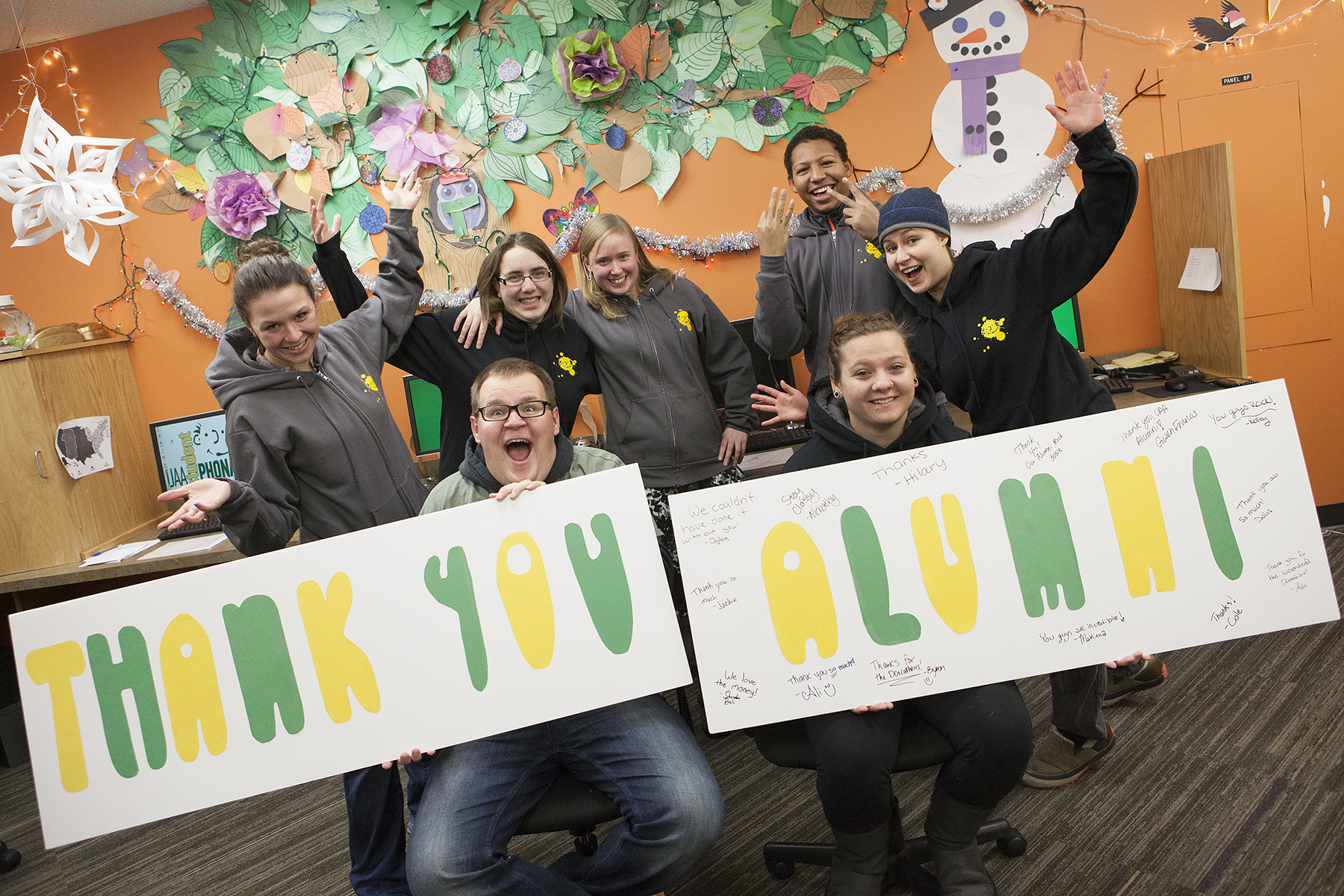 UAA Phonathon students holding Thank You sign