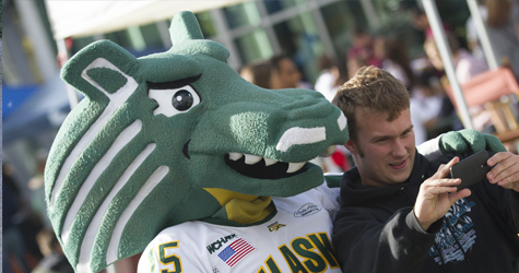 UAA Student taking a selfie with Spirit Mascot at UAA Campus Kickoff