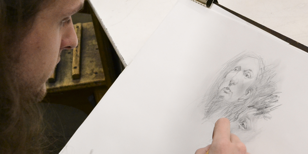 Student working on sketch of man's head