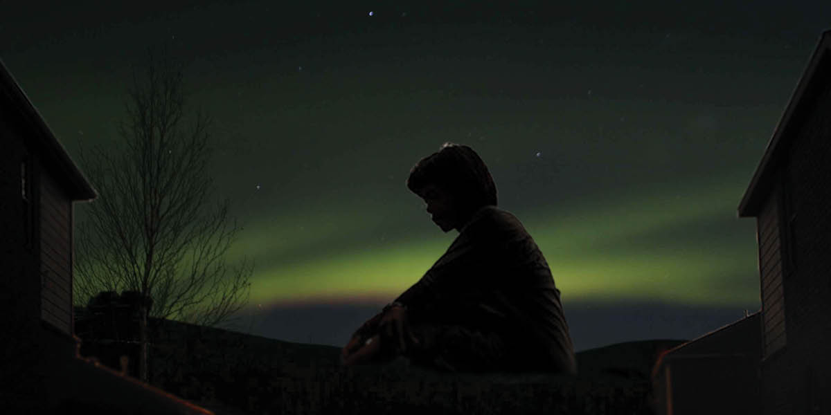 Silhouette of a sitting boy against the aurora