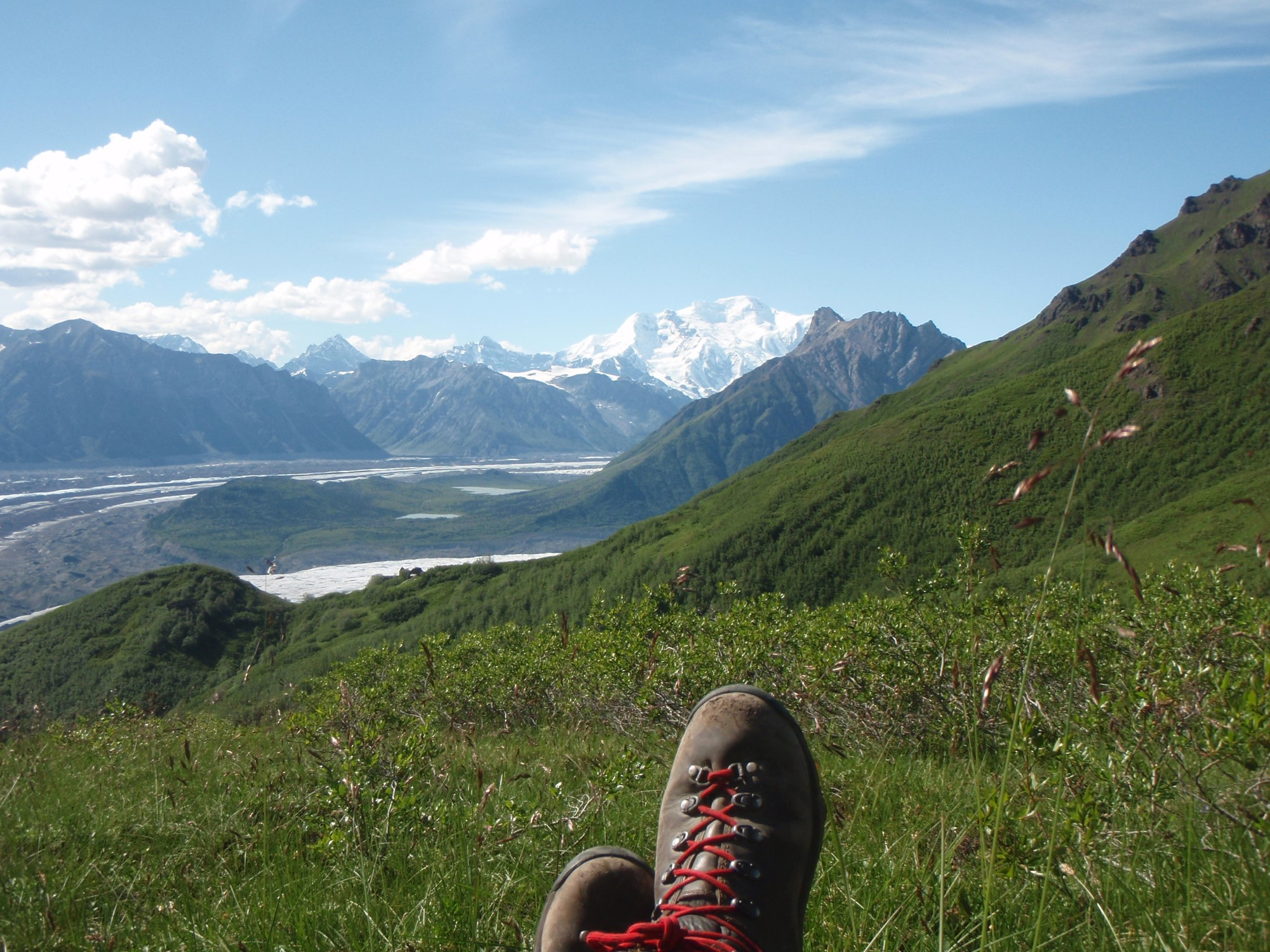 Relaxing few of an Alaskan valley with a pair of hiking boots