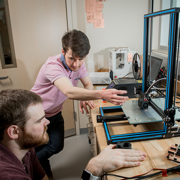 UAA Robotics Club members use a 3D printer to fabricate parts for the team's new rover in the robotics lab in UAA's Engineering and Industry Building