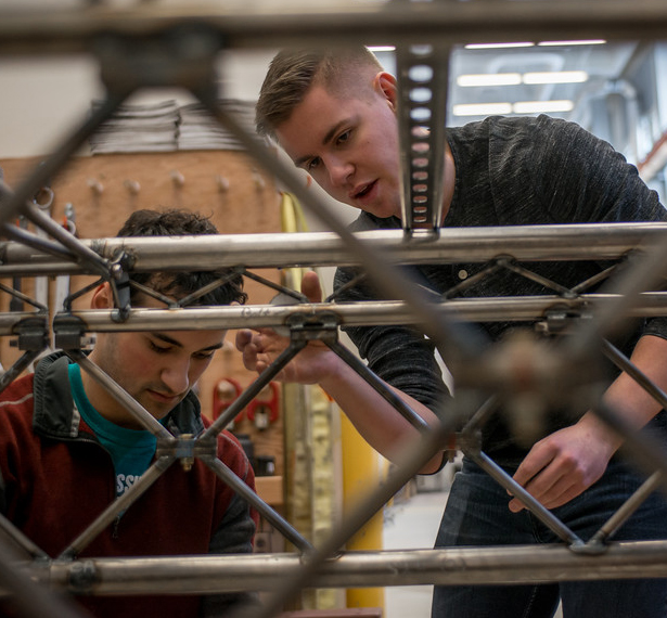 Zach Cuddihy, right, and Aaron Murphy, left, prepare the UAA team's entry in the 2018 American Society of Civil Engineers (ASCE) Student Steel Bridge competition for load testing.