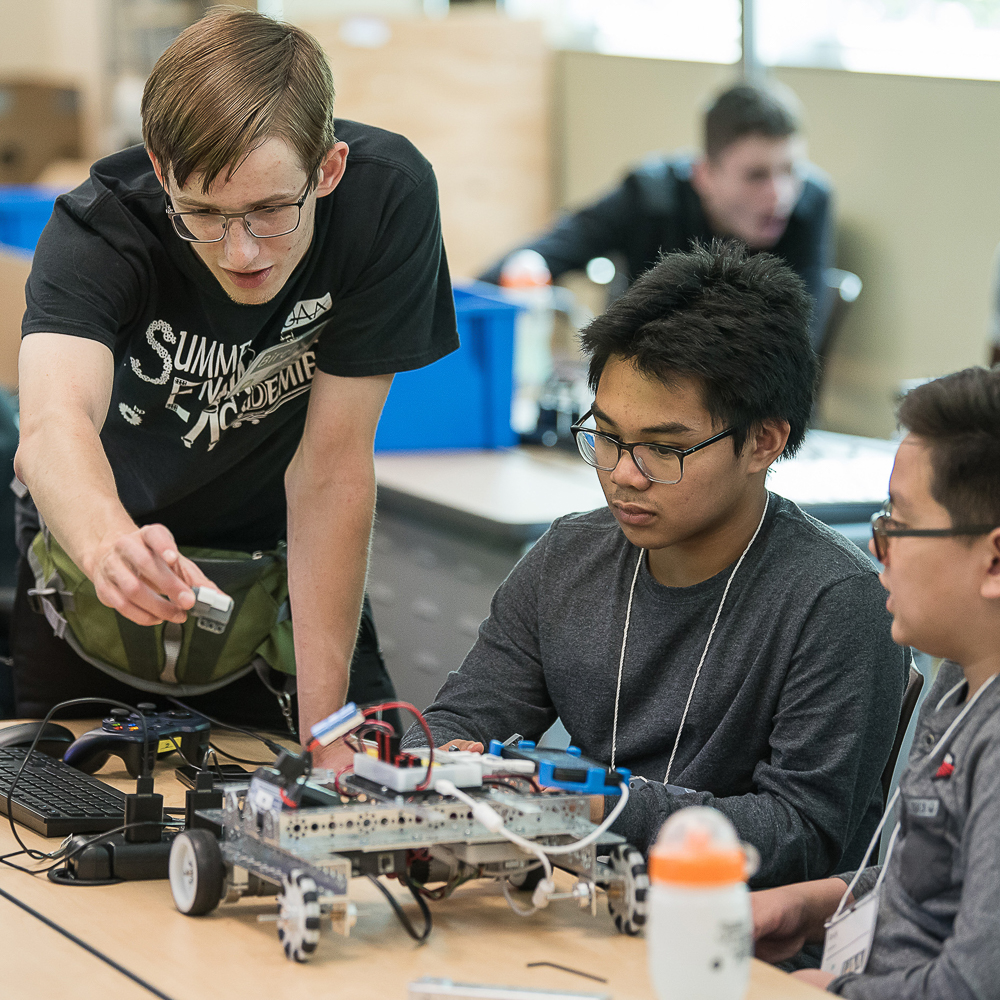engineering student helping two kids build a robot