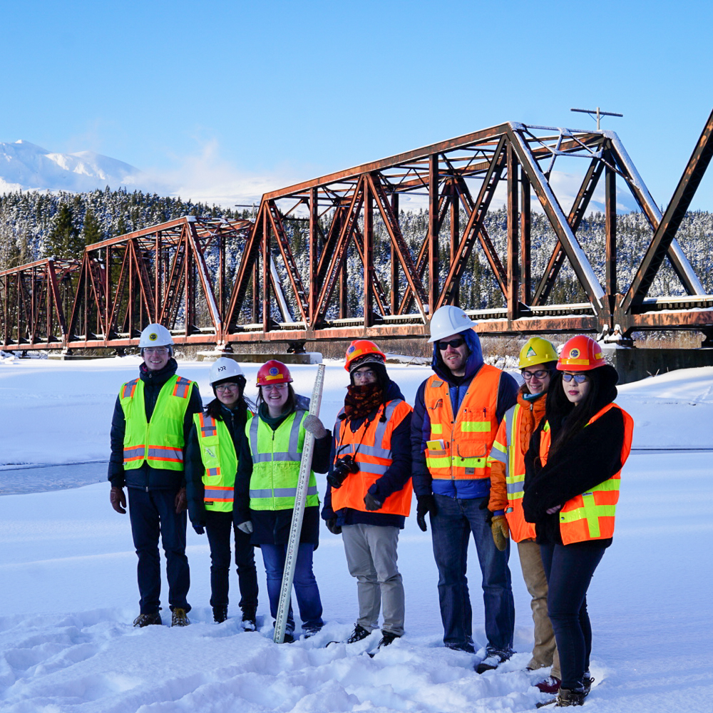 Group of students in reflective vests and hard hats in front of a bridge and mountains