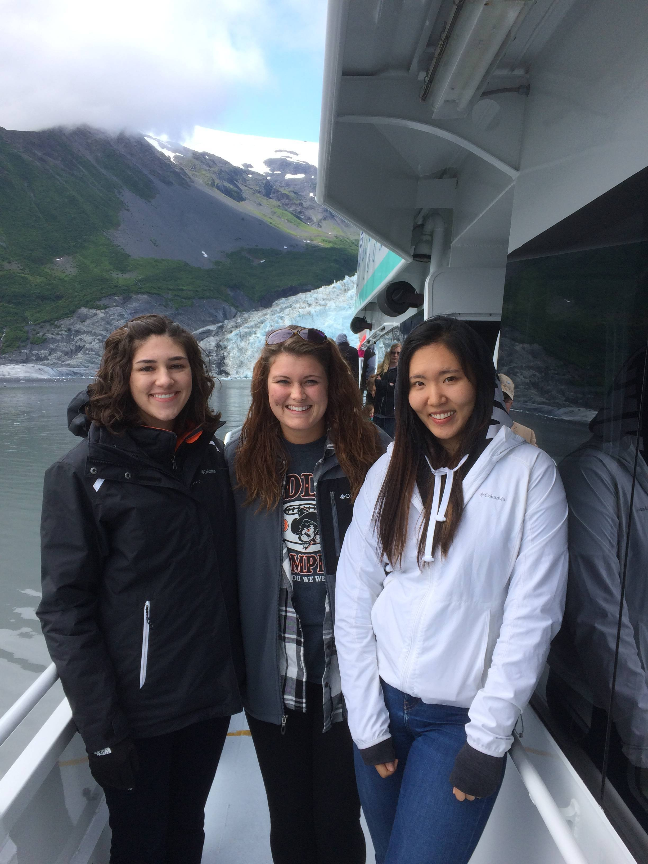 Three girls smiling in front of glacier
