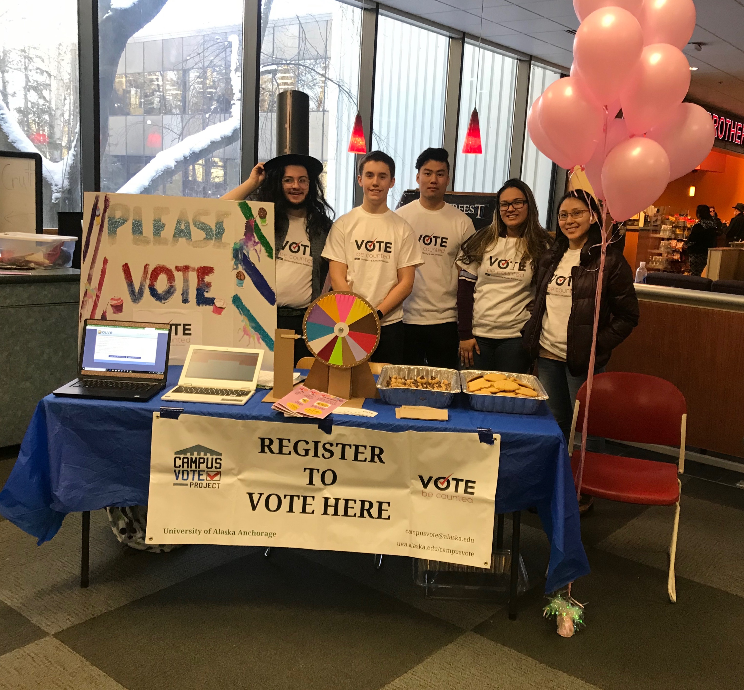 A group of students stands behind a table with information about voter registration