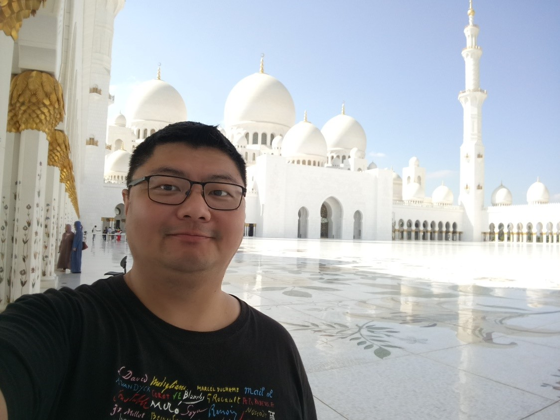 A photo of Tzu-Chiao Chen standing in front of the Sheikh Zayed Grand Mosque in Abu Dhabi, UAE