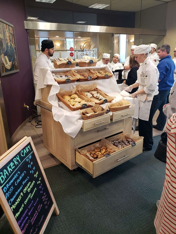 People lined up to purchase baked goods from UAA Culinary Students bakery cart