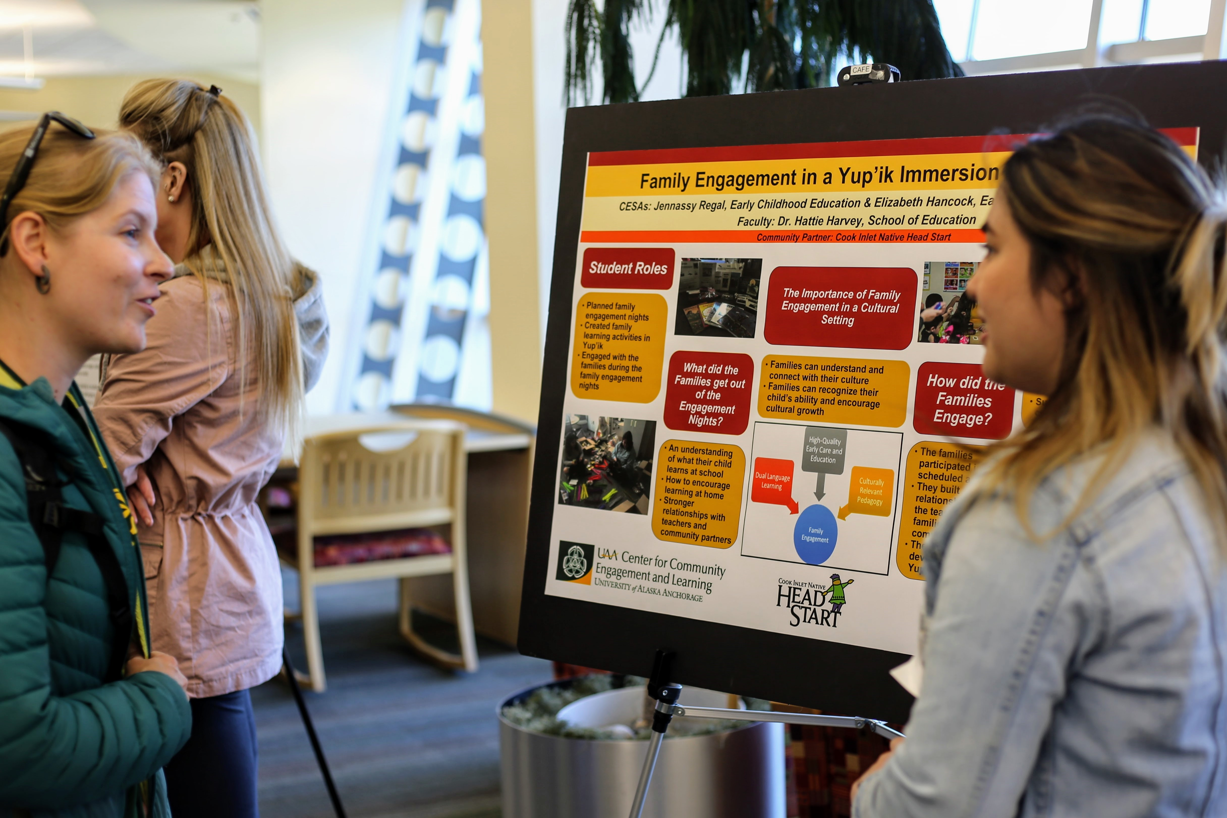 A blonde women with light sking talks to a student with dark hair standing next to her CESA poster.