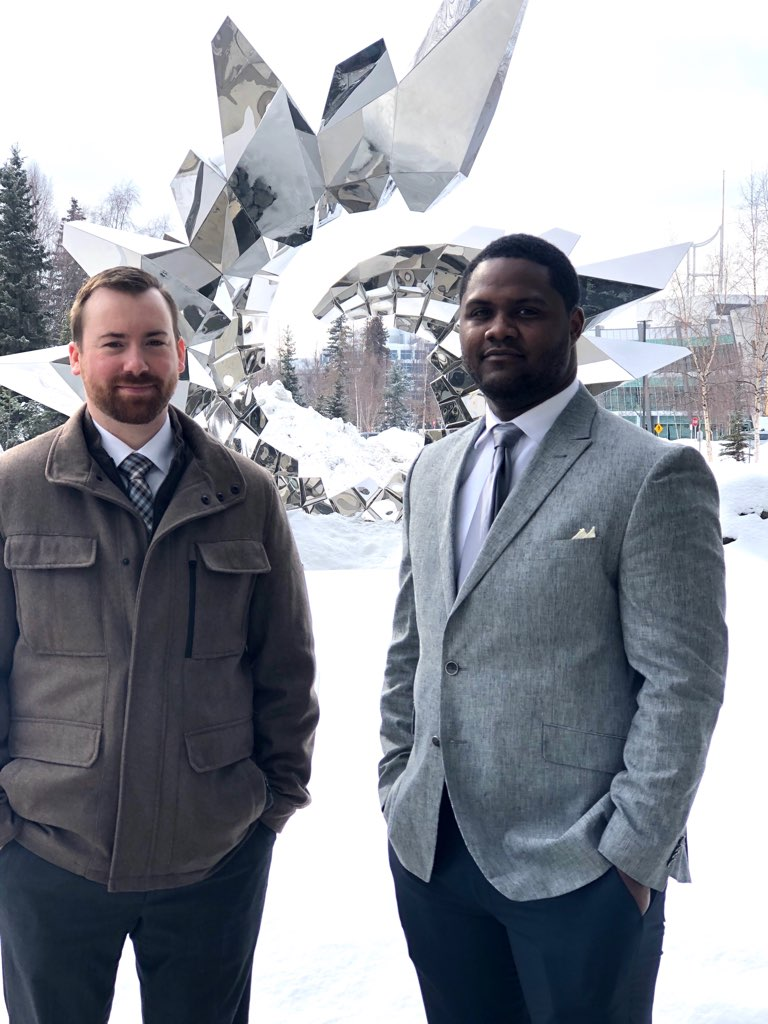A white man and a black man stand outdoors in front of a large metal, circular sculpture with snow covering the snow behind them.