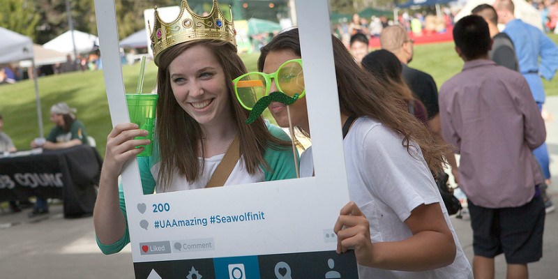 Students take instagram photo at campus event.