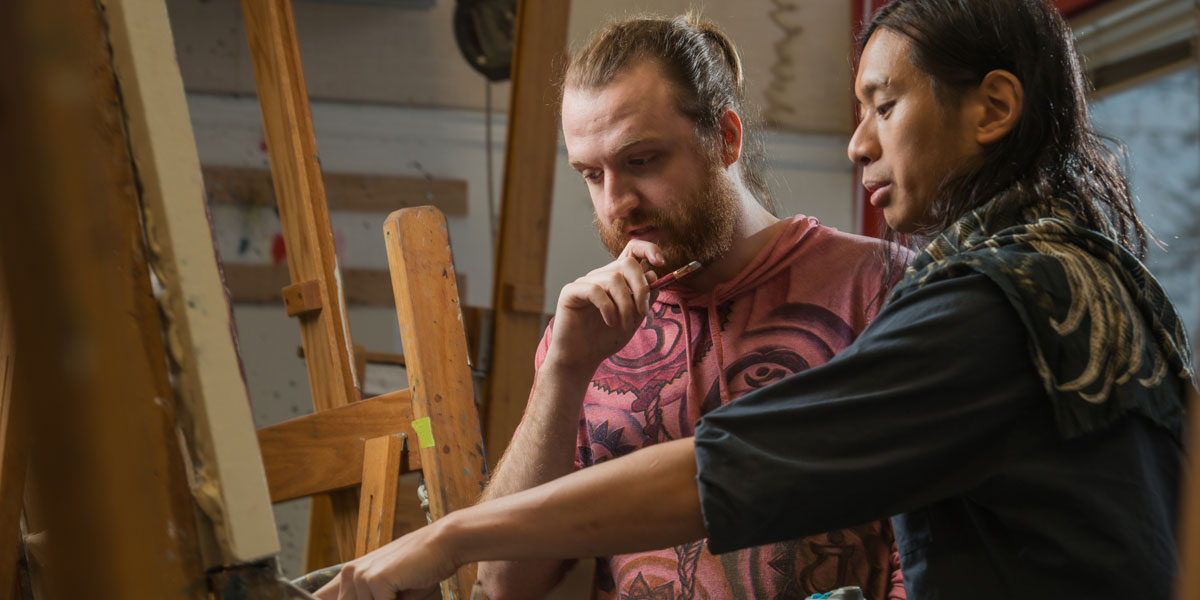 A student discusses their painting with their instructor