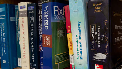 Various pharmaceutical text books on a shelf