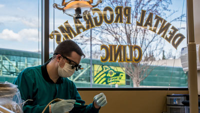 A dental student working in front of the dental clinic sign