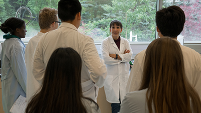A group of students in lab coats gather in a circle