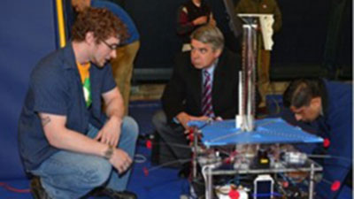 Nick explains the Explorer robot to Eric Evans, Director of the MIT Lincoln Laboratory.
