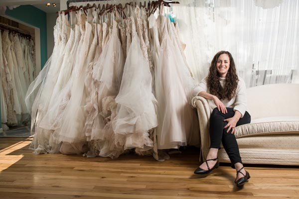Business owner sitting next to products (dresses)