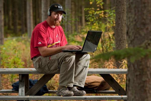 Person sitting on a table in the woods while working on a laptop with a headset