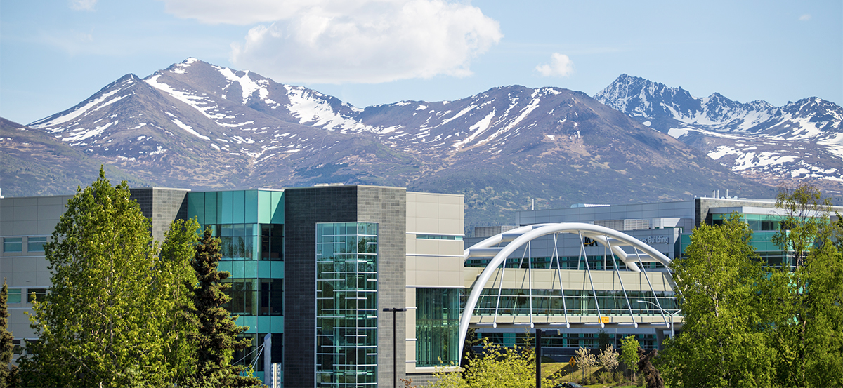 Summer view of UAA bridge with Chugach mountains behind.