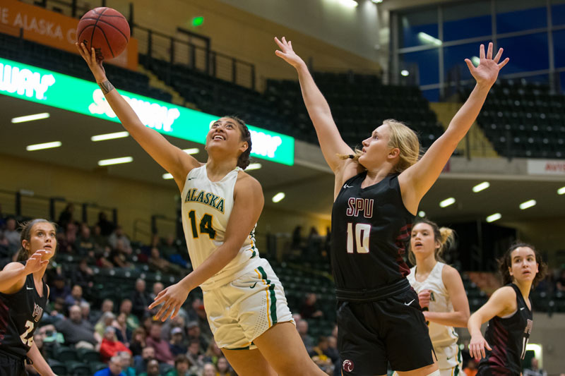 UAA women's basketball player jumps for a layup