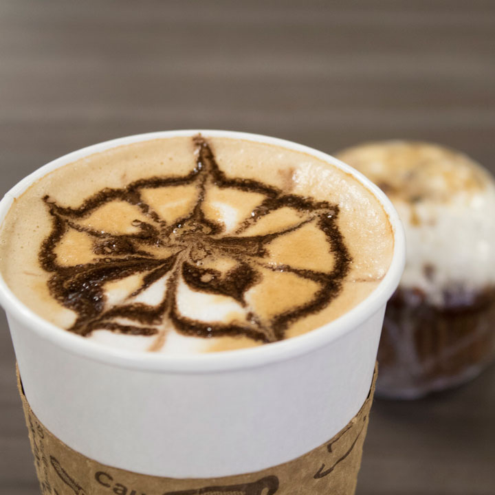 Latte with foam art and muffin behind it
