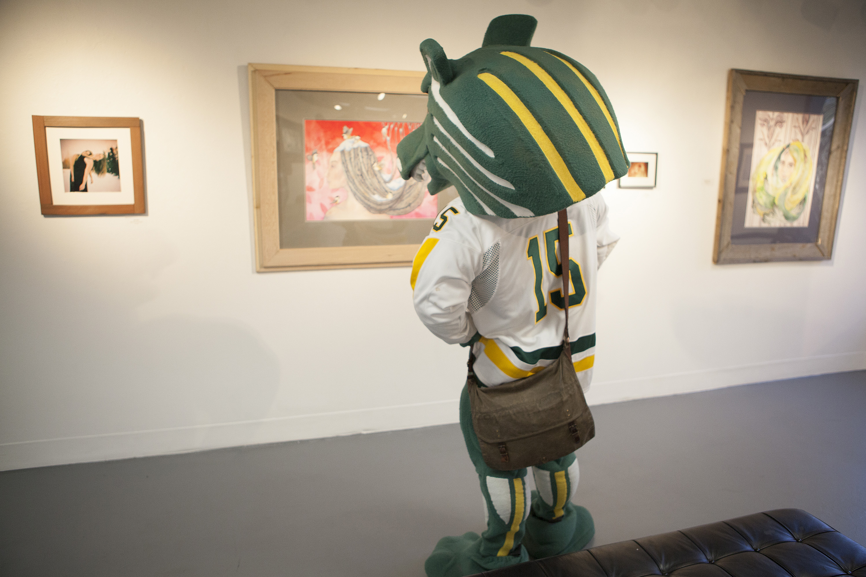 Spirit the Seawolf checks out fine art in one of UAA's art galleries.