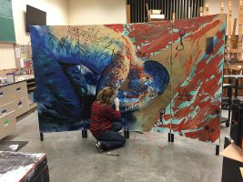 UAA art student Katherine Massong paints a portrait for the ACE's Mural Project.