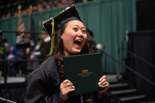 Jacqueline Yi, B.S. Nursing Science, shows off her degree during UAA's 2019 Fall Commencement at the Alaska Airlines Center.
