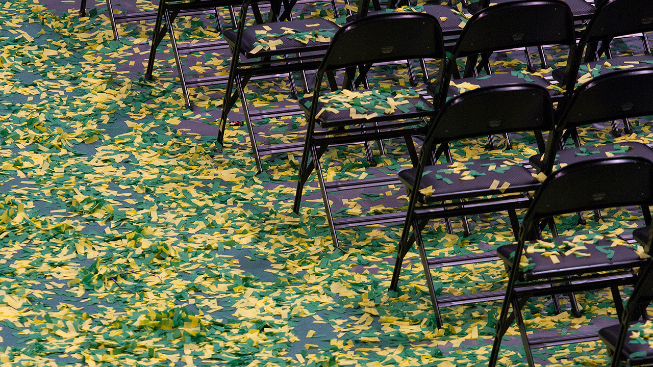Green & gold confetti adorns the Alaska Airlines Center following UAA Commencement