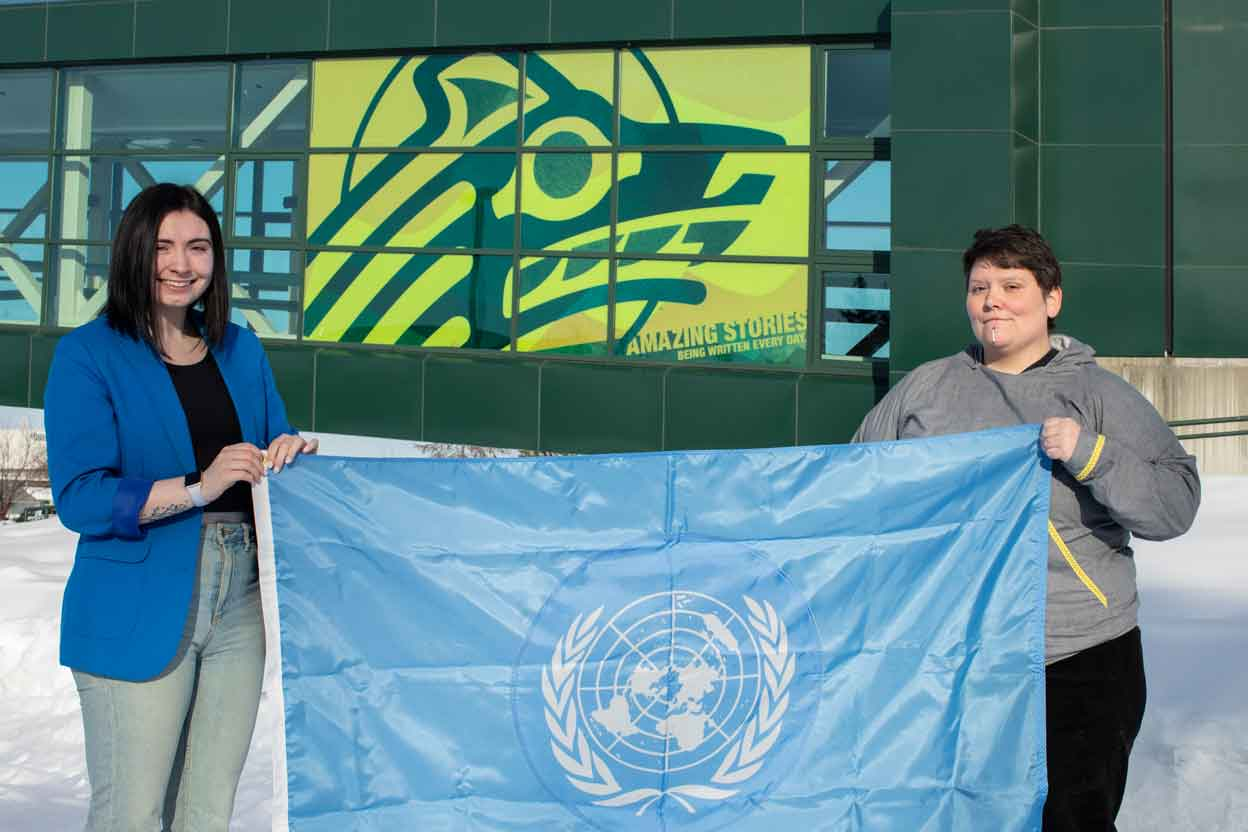 Abbie Lampman and Marya Halvorsen hold the flag of the United Nations.