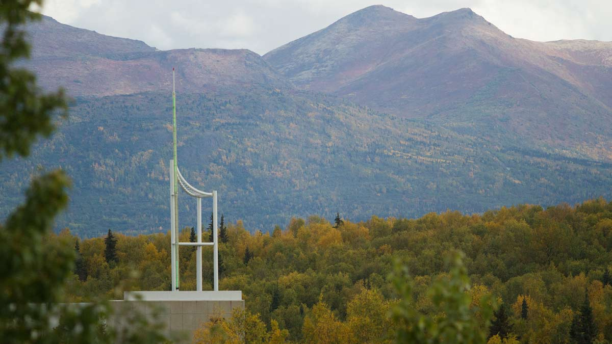 Spire atop UAA's Consortium Library with Chugach Mountains in background.