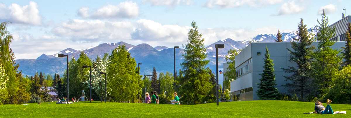 UAA campus in summer with mountains in background.