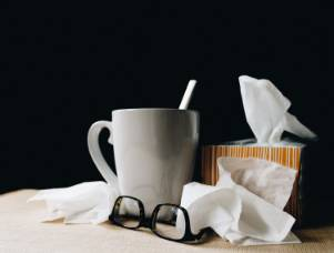 Cup with tissues and glasses beside