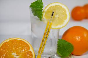 glass of water with oranges and thermometer