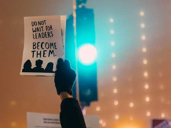 "Person holds sign reading ""Do not wait for leaders. Become them."" Photo by rob walsh on Unsplash."