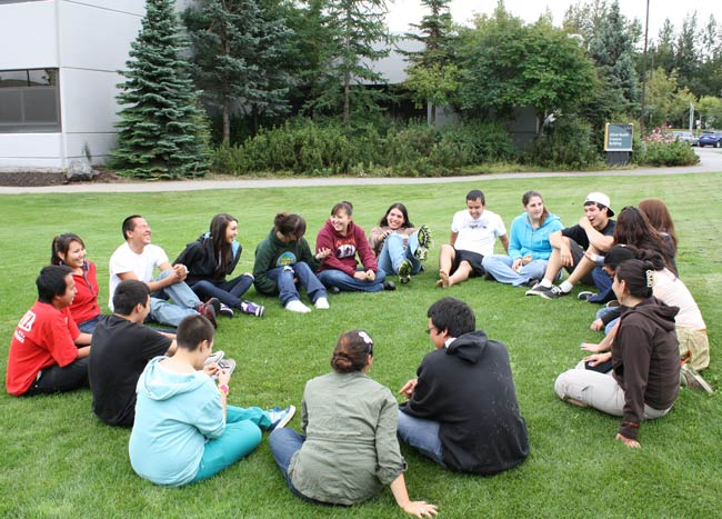 NET program participants sit on the grass in a circle