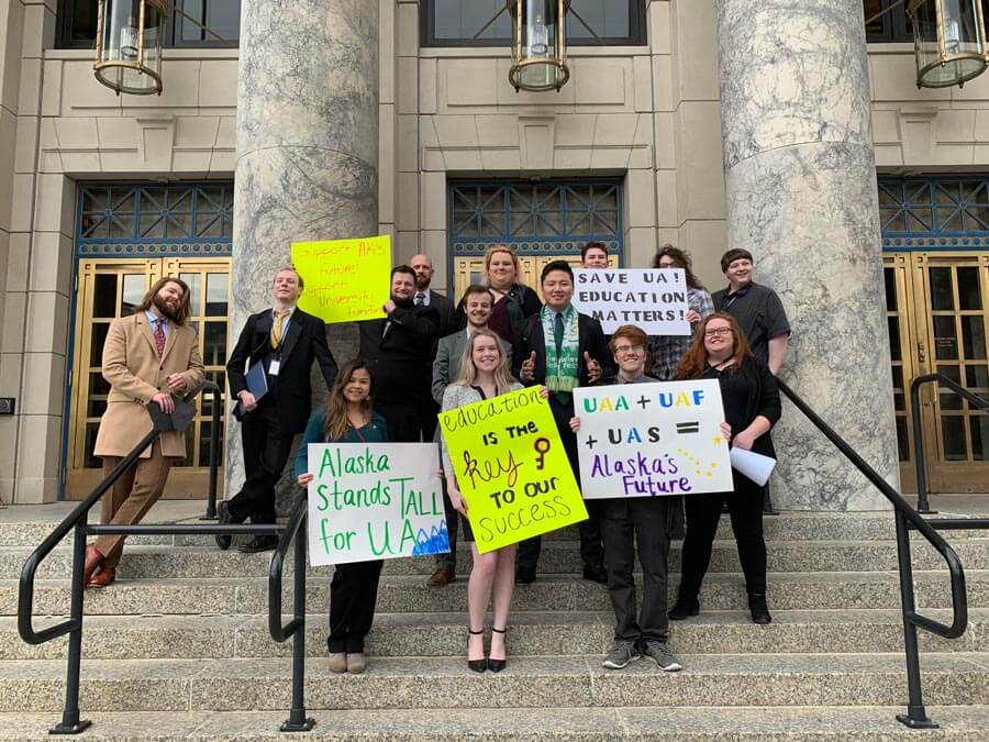 Student leaders pose with pro-university signs in front of Alaska capitol