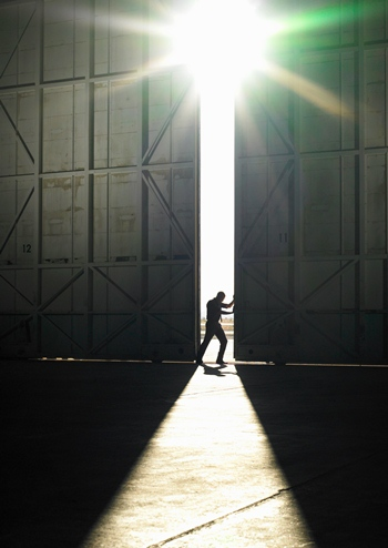 Military man opening warehouse door